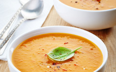 two bowls of squash soup on wooden table