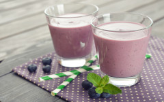 Blueberry smoothie with fresh berry and drink straws on wooden background