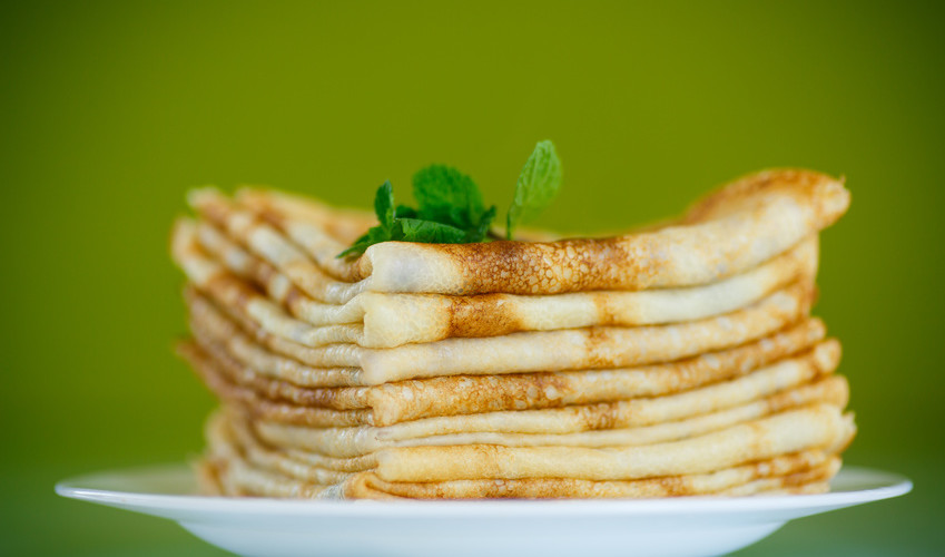 many thin pancakes on a plate on a green background